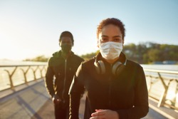 Jogging during quarantine. Young african couple wearing face medical masks while running together on the bridge in the morning. Sport and coronavirus. Covid-19. Protection. Social distancing