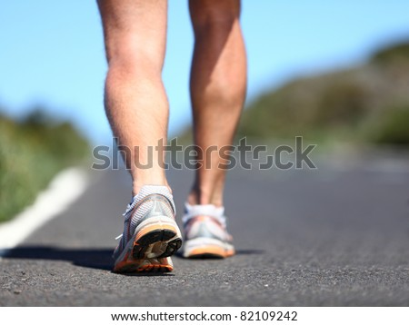 Jogging man. Running shoes and legs of male runner outside on road.
