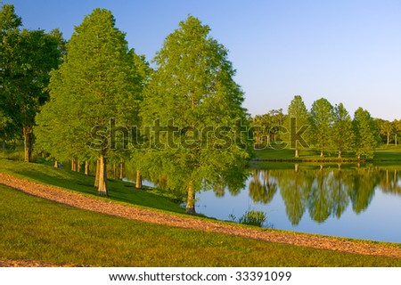 Jogging path around lake with trees.