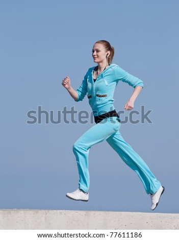 Jogging. Running woman against the blue sky.