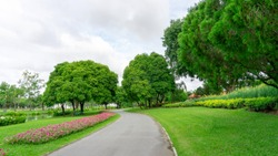Jogging track in garden of public park among greenery trees, flower shrub and bush, black asfalt concrete walkway beside green grass lawn under cloudy sky in a good care maintenance landscapes
