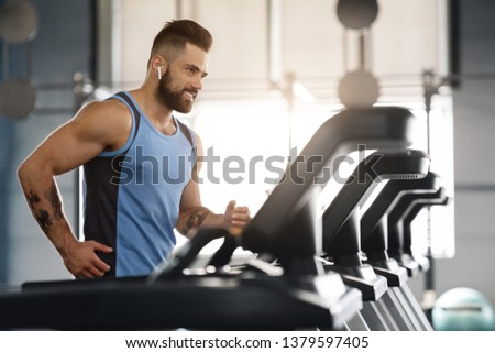 Jogging with pleasure. Young handsome man in modern wireless headphones smiling, running on treadmill at gym, free space