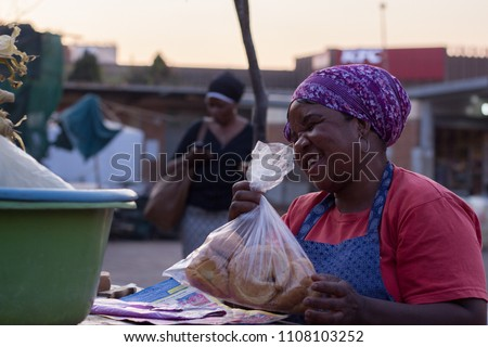 Johannesburg, South Africa, Circa May 2016. A photographer, not visible captures a candid photograph of an African women laughing while holding a plastic packet filled with bread rolls. #1108103252
