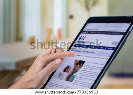 Johannesburg, South Africa 12/10/2017 Illustrative Editorial Close up Demonstrating a father using a digital tablet computer to do research online; Father searching for baby information online