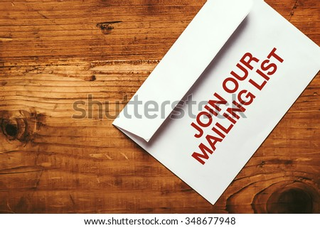 Join our mailing list imprint stamp on white paper envelope placed on top of office desk, top view