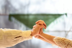Joined and intertwined hands of a couple dressed in white.