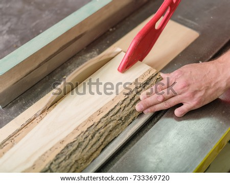 Joiner saws timber beam on a circular saw