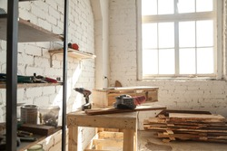 Joinery shop interior with tools and supplies, woodwork machines and equipment, instruments on workbench, starting small carpentry workshop business concept, making wooden ware, custom made furniture