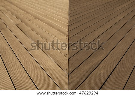 Joint area of wooden deck flooring with small grooves in distinctive lighting condition.
