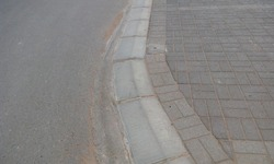 Joint of tarmac road and Interlock tiles by 300mm high Kerb stones for the protection