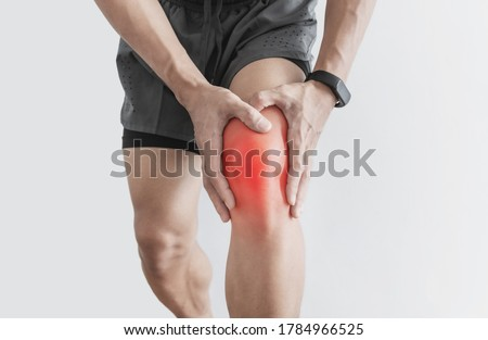 Joint pain, Arthritis and tendon problems. a man touching nee at pain point, isolated on white background