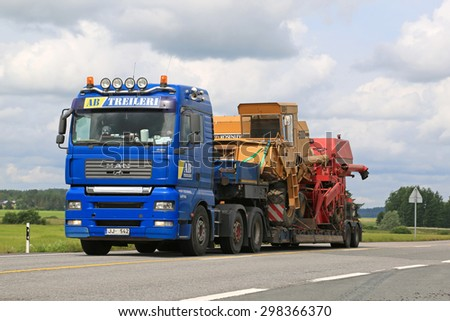 JOKIOINEN, FINLAND - JULY 18, 2015: MAN truck hauls combine harvesters on low floor trailer. Abnormal transport permit is required, if any dimension of the transport exceeds the free dimension limits.