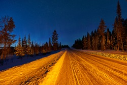 Jokkmokk, Sweden - 03 02 2019: road to Jokkmokk before Polecirkeln-Arctic Circle. northernlights showed short time while roadtrip to the north at mainroad. Stopped to make photos with warninglamps on.