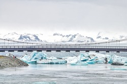 Jokulsarlon glacial lagoon, glacial lake in Iceland with many icebergs floating, route one 1 bridge over water with people, Vatnajokull mountains, cliffs, snow, clouds