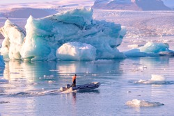Jokulsarlon glacier lagoon in Iceland. Blue icebergs and tour boat on lake water. Northern nature landscape in Vatnajokull National Park