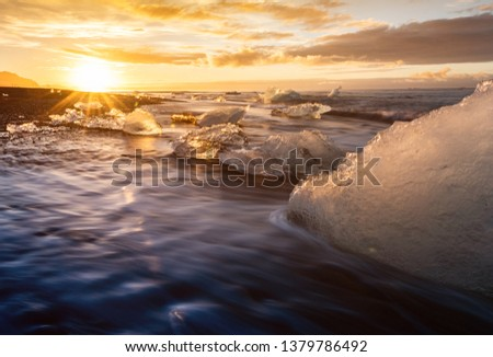Stock Photo Jokulsarlon Glacier Lagoon. Jökulsárlón is a must stop for any tourist visiting Iceland. Icelandic sun contrasts the icy waters of the glacial ocean bay as the golden summer sun melts the ocean ice.