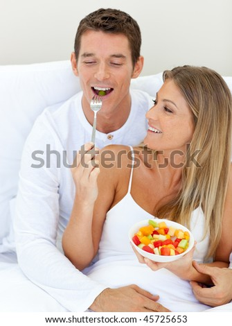 Jolly couple eating fruit lying on their bed at home