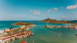 Jolly Harbour view in Antigua with tropical nature, beach houses, island view, sailboats anchoring in a bay, Caribbean sea, in the blue water, lagoon, sailing in the Caribbean islands, properties