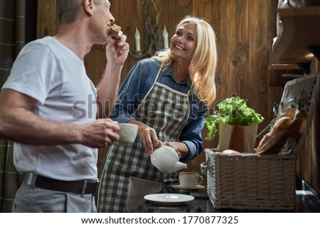 Jolly mature female is pouring hot drink in cups while man is eating sandwich in wooden kitchen