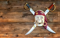 Jolly pirate scull in bandanna with crossed swords and golden teeth on wooden background. Dead bone skeleton.