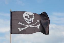 Jolly Roger flag against blue sky