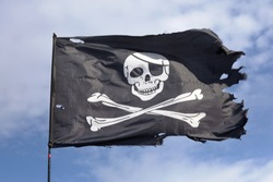 jolly roger. pirate flag.Against the background of blue sky.
