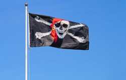 Jolly Roger pirate flag and blue sky.