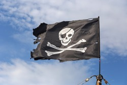 Jolly Roger pirate flag on blue sky background.