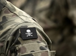 Jolly Roger pirate flag on military uniform. A skull and crossbones or death's head a symbol of death.