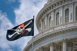 Jolly Roger Pirate flag waving on Washington DC Capitol detail on cloudy sky