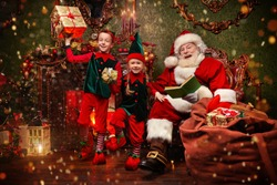 Jolly Santa Claus and his elves are preparing gifts for Christmas at home. Merry Christmas and Happy New Year!