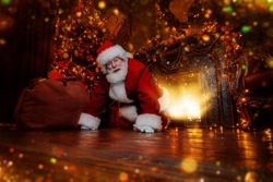 Jolly Santa Claus sneaked into the house through the fireplace with a bag of gifts. Beautiful home decoration. Merry Christmas and Happy New Year!