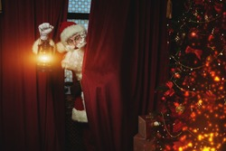 Jolly Santa Claus sneaks into the house through the window, he looks out from behind the curtains with a lantern. Christmas and New Year concept.