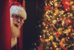 Jolly Santa Claus sneaks into the house through the window, he sits on the windowsill and peeks out from behind the curtains. Christmas and New Year concept.