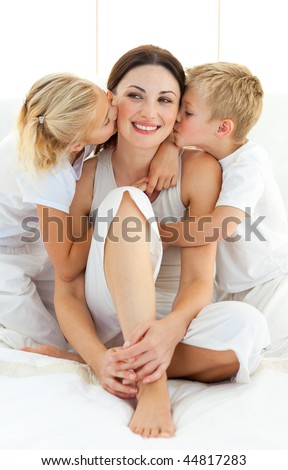 Jolly siblings kissing their mother sitting on a bed at home - stock photo