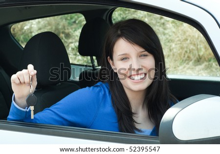 Jolly teen girl sitting in her car holding keys after bying a new car