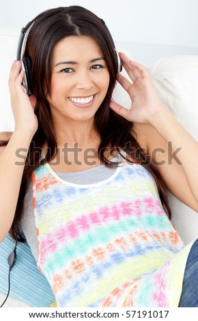 Jolly woman with headphones on lying on a sofa in a living-room