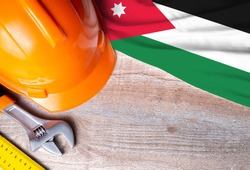 Jordan flag with different construction tools on wood background, with copy space for text. Happy Labor day concept.