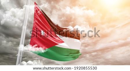 Jordan national flag cloth fabric waving on beautiful grey sky.  Stock photo ©