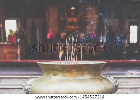 Praying with yellow joss sticks in the buddha temple Images