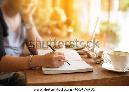 journalist hand writing article for newspaper on wooden workspace and cross process and soft flare filter