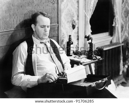 Journalist sitting on his bed with a typewriter, typing