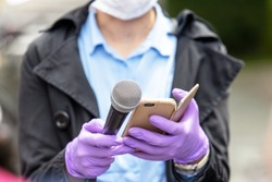 Journalist wearing protective gloves and face mask against coronavirus COVID-19 disease holding microphone making media interview during virus pandemic