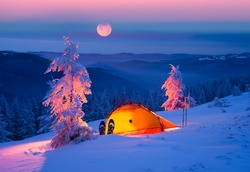 Journey through the winter alpine forests in the wild mountains of Ukraine photographic artist climber tourist equipment, powerful lantern fantasy turns the winter forest into a fairy tale