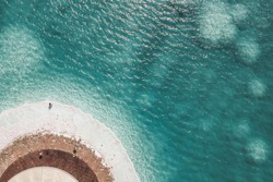 Journey to the shores of the Dead Sea. Shooting from the drone. The girl walks along the salt coast.