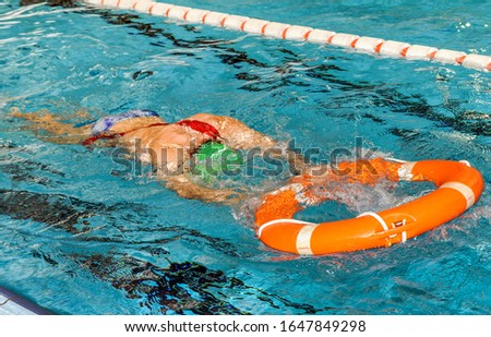 Joven deportista nadando en una piscina con un flotador salvavidas