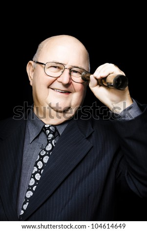 Jovial elderly businessman acting with forethought and intelligence looks through a telescope searching for future business opportunities and strategies