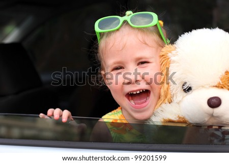 joy a child looks out from a car window, holding a toy