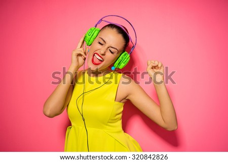 Joy and music. Colorful studio portrait of happy young brunette woman with earphones is dancing and singing.