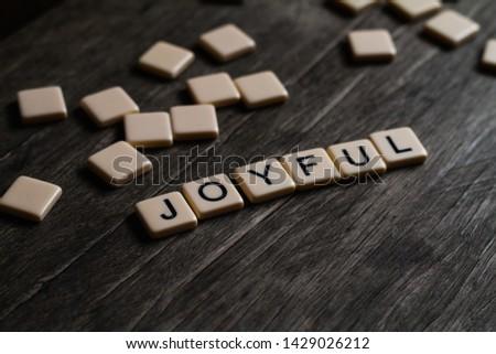 Joy/Joyfulness/Joyful spelt out using tiles on a timber surface #1429026212